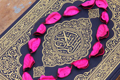 Libro sacro del Corano con le foglie del fiore Fotografia Stock Libera da Diritti