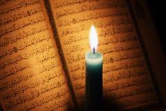 Libro sagrado del Corán o del quran con la vela en luz de una vela Imagen de archivo libre de regalías