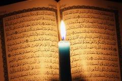 Libro sagrado del Corán o del quran con la vela en luz de una vela fotografía de archivo libre de regalías