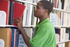 Libro slecting dello studente universitario dallo shel delle biblioteche Immagine Stock