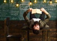 Libro sovraccarico esaurito di studio e di lettura del giovane sulla tavola nella sala Immagine Stock Libera da Diritti