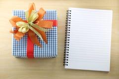 Libro vacío y caja de regalo azul en el piso de madera Fotografía de archivo