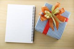 Libro vacío y caja de regalo azul en el piso de madera Fotos de archivo