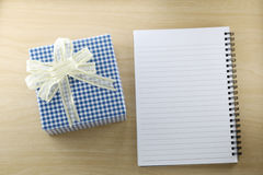Libro vacío y caja de regalo azul en el piso de madera Fotos de archivo libres de regalías