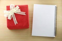 Libro vacío y caja de regalo roja en el piso de madera Fotos de archivo