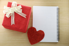 Libro vacío y caja de regalo roja en el piso de madera Imagen de archivo libre de regalías