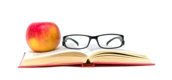Libro, vetri e mela su una priorità bassa bianca Fotografia Stock Libera da Diritti