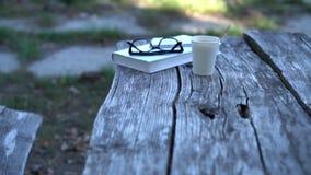 Libro, vidrios de lectura y café para llevar metrajes