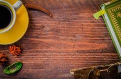 libro, vidrios, y taza de café en la tabla de madera al aire libre por la mañana t Imagen de archivo
