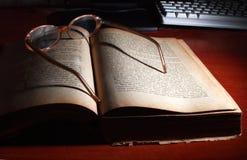 Libro, vidrios y teclado de ordenador. Imagen de archivo libre de regalías