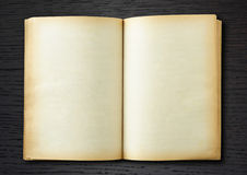 Libro viejo abierto en fondo de madera oscuro Foto de archivo