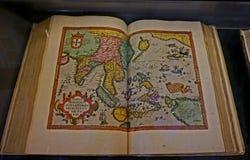 Libro viejo abierto en los mapas del mundo en el escaparate del pasillo de la biblioteca austríaca nacional en el palacio de Hofb fotografía de archivo