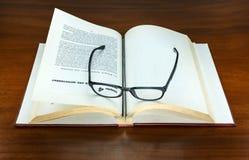 Libro viejo abierto y lentes Fotos de archivo libres de regalías