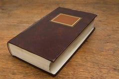 Libro viejo cerrado en un vector de madera Fotos de archivo