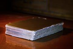 Libro viejo en una tabla en la sala de estar oscura Fotos de archivo