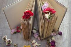 Libro viejo que se coloca en la tabla de madera y rosas secadas Fotografía de archivo