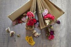 Libro viejo que se coloca en la tabla de madera y rosas secadas Imagen de archivo libre de regalías