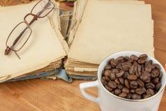 Libro viejo y una taza de granos de café en la tabla Lectura de los libros viejos Foto de archivo libre de regalías