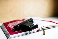 Libro y bala negros de arma Concepto de la novela detective imagen de archivo