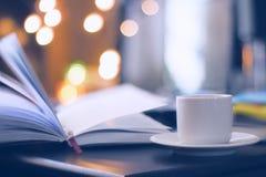 Libro y café con el fondo mágico del bokeh Fotos de archivo