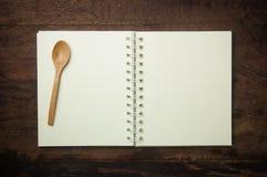 Libro y cuchara de la receta Fotos de archivo libres de regalías