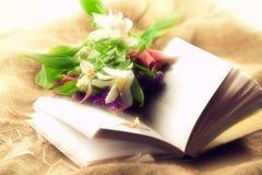 Libro y flores Imagenes de archivo