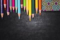 Libro y lápices coloreados en la pizarra imagen de archivo