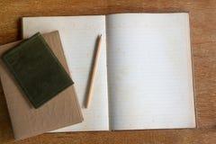 Libro y lápiz del diario en la tabla de madera Imágenes de archivo libres de regalías