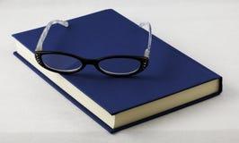 Libro y lentes Imagenes de archivo