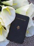 Libro y lirios de rezo del bolsillo Imagen de archivo libre de regalías