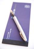 Libro y pluma de cheque. Fotografía de archivo libre de regalías