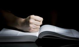 Libro y puño Imagen de archivo libre de regalías