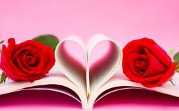 Libro y rosas en forma de corazón Fotos de archivo