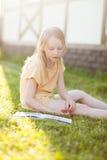 Libro y sentada de lectura hermoso del adolescente en hierba verde Foto de archivo