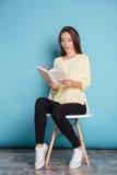 Libro y sentada de lectura pensativo de la muchacha en silla Fotos de archivo libres de regalías