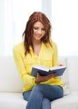 Libro y sentada de lectura sonriente del adolescente en el sofá Fotografía de archivo