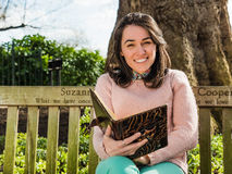 Libro y sonrisa de lectura joven de la mujer de la belleza asentados en banco de parque Foto de archivo libre de regalías