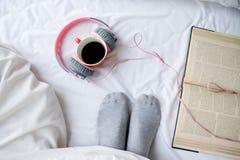 Libro y taza de café en la cama blanca con el espacio de la copia Imagenes de archivo