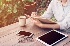 Libro y teléfono, tableta de la escritura de la mano de la mujer en la tabla en jardín en Fotos de archivo