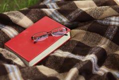 Libro y vidrios en la tela escocesa, leyendo Imagen de archivo