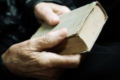 Libro y viejas manos foto de archivo