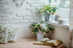 Libros, almohadas en la esquina de la lectura dentro de la casa Imagen de archivo libre de regalías