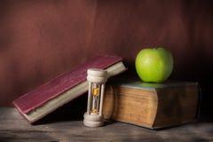 Libros antiguos con la manzana y el reloj de arena. Fotografía de archivo