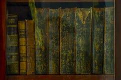 Libros antiguos en estante en la biblioteca fotos de archivo