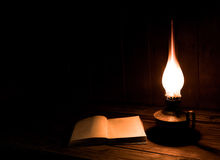 Libros antiguos viejos con la lámpara ardiente de la parafina cerca en la tabla de madera Imágenes de archivo libres de regalías