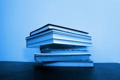 Libros apilados en una tabla imagenes de archivo