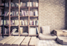 Libros borrosos en el estante con la pared de ladrillo en biblioteca pública Imagenes de archivo