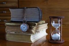 Libros con el reloj del reloj de arena y del bolsillo Fotos de archivo libres de regalías