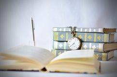 Libros con el reloj viejo Fotografía de archivo libre de regalías
