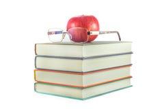Libros con la manzana roja y vidrios en un fondo blanco Imagen de archivo libre de regalías